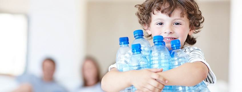 Little boy holding many plastic bottles of water.
